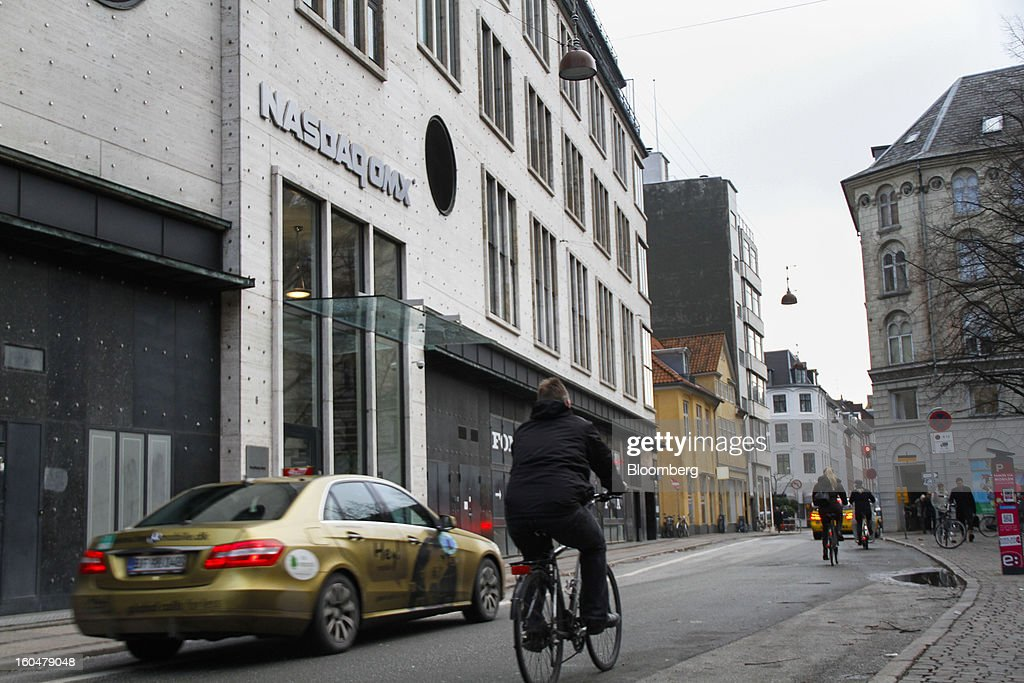 Cyclists pass a Nasdaq OMX sign above the entrance to the Copenhagen Stock Exchange in Copenhagen, Denmark, on Friday, Feb. 1, 2013. Danish regional banks are struggling to emerge from a burst property bubble that's forced the government resolution agency to take over a dozen lenders after losses on commercial and agricultural loans wiped out capital. Photographer: Freya Ingrid Morales/Bloomberg via Getty Images