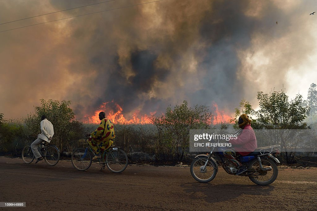 Cyclists pass a sugar cane field burning before the sugar cane harvest on January 23, 2013 near Niono, 370 kilometres north of the capital Bamako. Malian soldiers have carried out multiple summary executions since the start of a French-backed offensive against Islamist extremists, a rights group charged on Wednesday. AFP PHOTO /ERIC FEFERBERG
