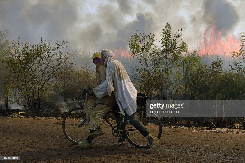Cyclists pass a sugar cane field burning before the sugar cane harvest on January 23, 2013 near Niono, 370 kilometres north of Bamako. Malian soldiers have carried out multiple summary executions since the start of a French-backed offensive against Islamist extremists, a rights group charged on Wednesday. AFP PHOTO / ERIC FEFERBERG