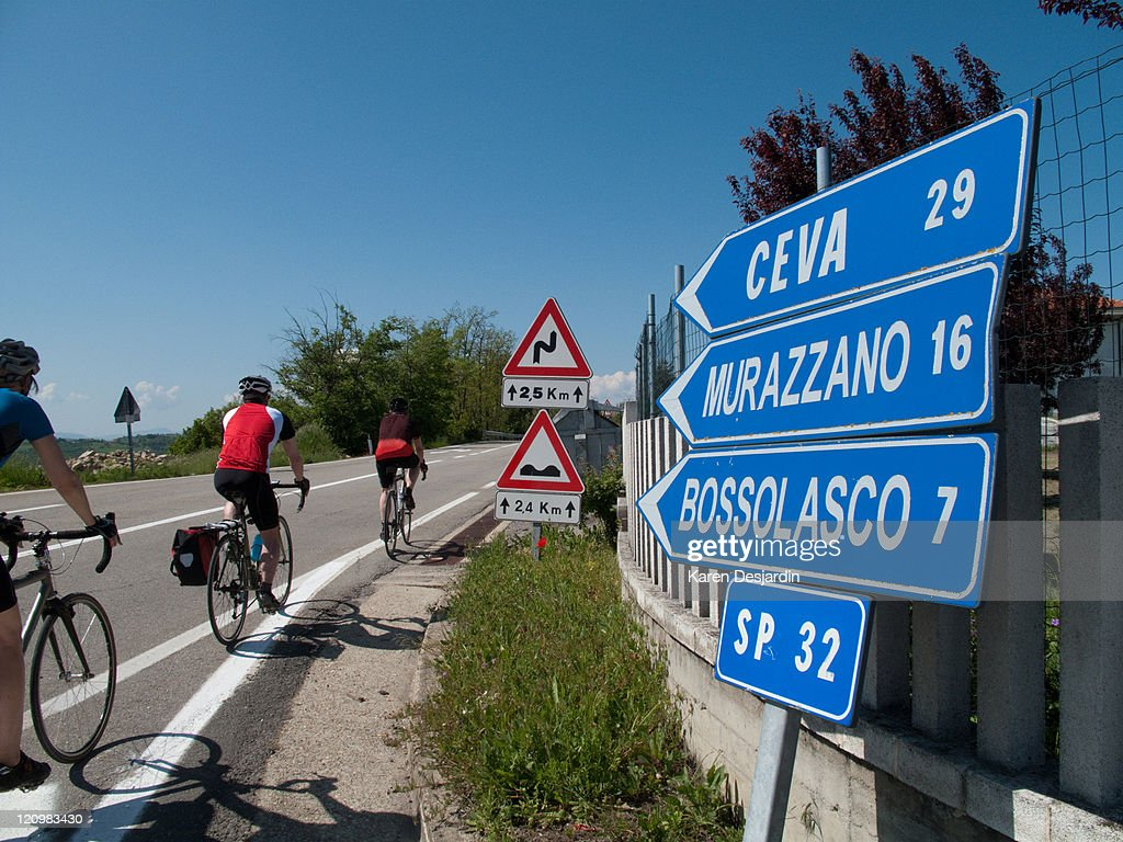Cyclists pass by directional road signs