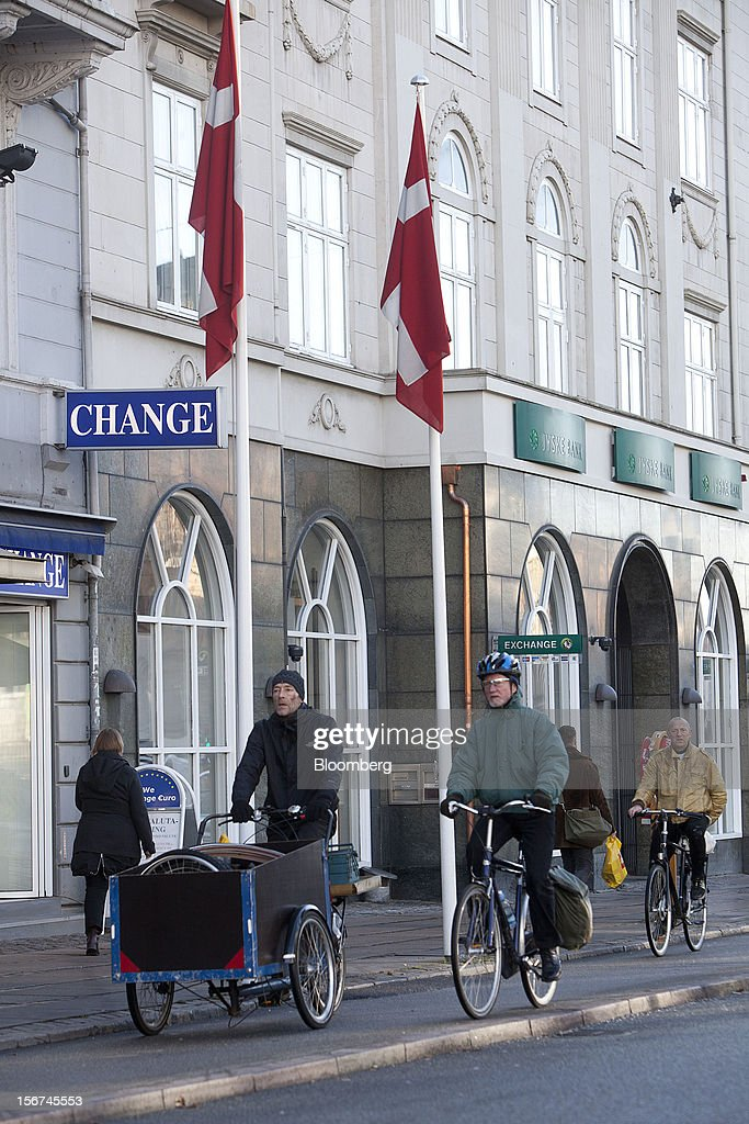 Cyclists pass Danish national flags hanging from flagpoles outside a money exchange in central Copenhagen, Denmark, on Monday, Nov. 19, 2012. Denmark's two-year yields sank to the lowest in almost three months in Copenhagen trading as Europe's debt crisis continues to drive investors north. Photographer: Linus Hook/Bloomberg via Getty Images