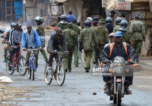 Cyclists pass Kenyan police officers patroling on August 12 2017 in the Kawangware neighborhood of Nairobi Eight bodies have been taken to the...