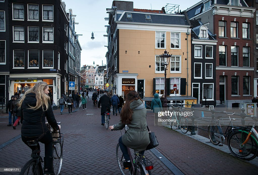 Cyclists pass over the Herengracht canal in Amsterdam, Netherlands, on Thursday, Jan. 2, 2014. The Netherlands will grow by 0.5 percent in 2014 as the world economy improves and consumer confidence picks up, the country's central bank forecast Dec. 9. Photographer: Jasper Juinen/Bloomberg via Getty Images