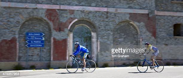 Cyclists pass signpost on The Stelvio Pass Passo dello Stelvio Stilfser Joch in Northern Italy