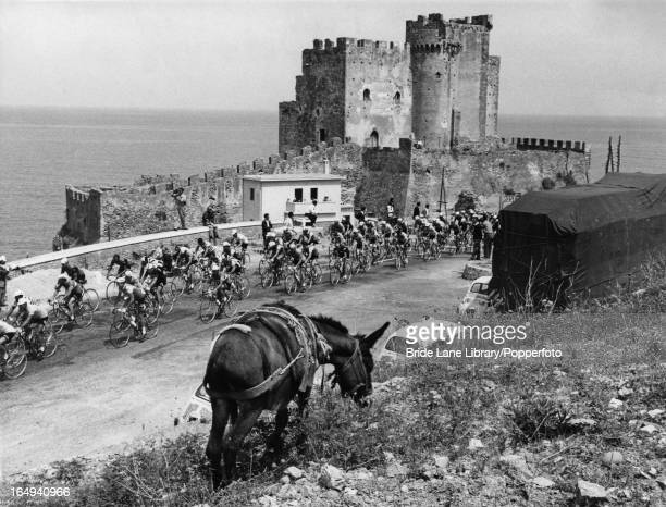 Cyclists pass the Capo Rizzuto on the Ionian coast in Calabria during the 7th lap of the Tour of Italy 29th May 1961