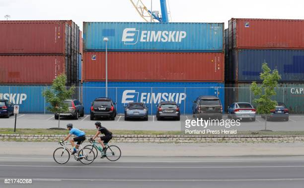 Cyclists pass the stacks of shipping containers at the International Marine Terminal Monday August 1 2016 in Portland Maine