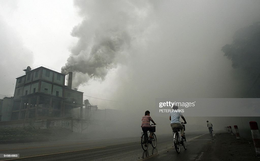 Cyclists pass through thick pollution from a factory in Yutian 100km east of Beijing in China's northwest Hebei province 18 July 2006 China's economy...