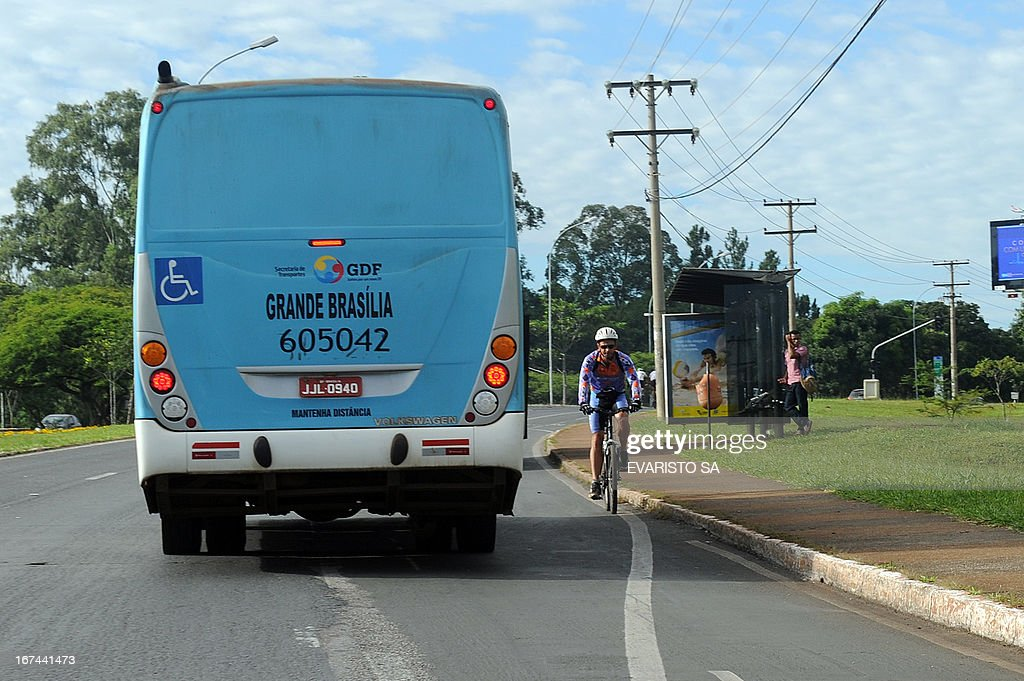 Cyclists pedal along a road without bikeways in South Lake in Brasilia, sharing the street with buses and cars, on April 16, 2013. AFP PHOTO/ Evaristo SA
