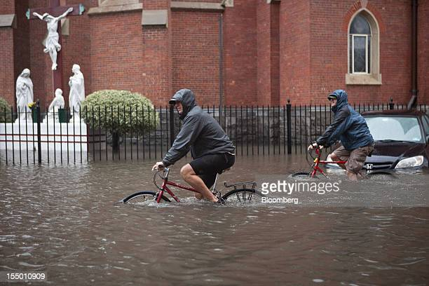 Cyclists peddle through flood waters in Hoboken New Jersey US on Tuesday Oct 30 2012 The Atlantic storm Sandy left a landscape of devastation across...
