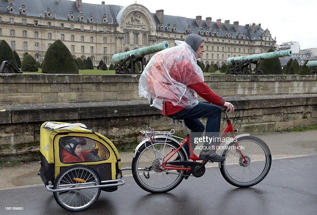 A cyclists pulls a trailer carrying children as they ride in front of the Invalides in Paris on April 9, 2013. AFP PHOTO / JACQUES DEMARTHON