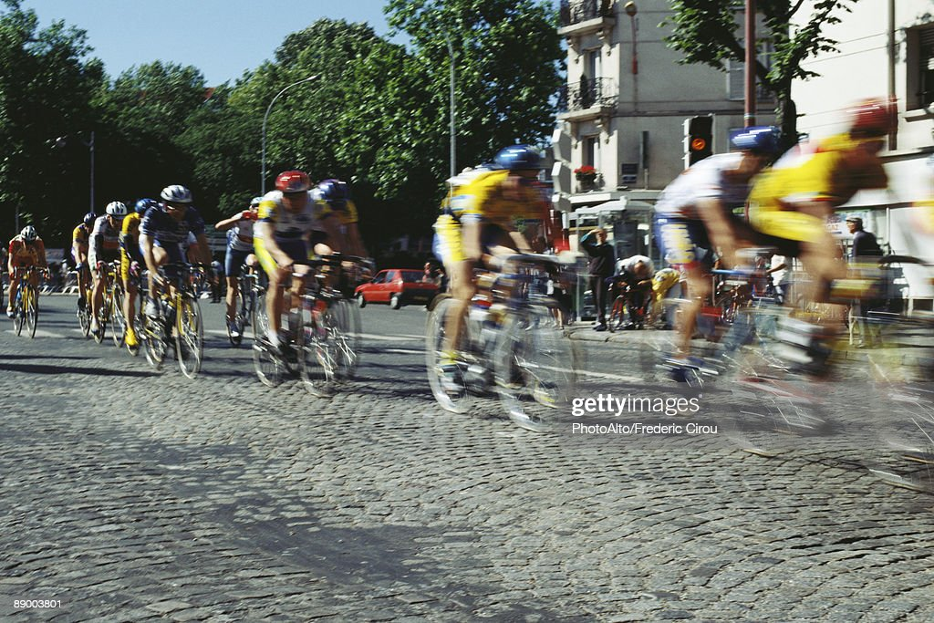 Cyclists racing on cobblestone street