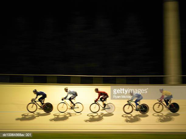 Cyclists racing on velodrome, side view