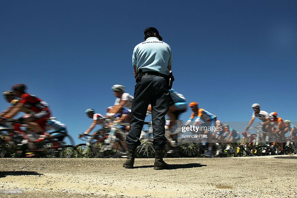 Cyclists ride by a gendarm on the course of Stage 14 of the Tour de France, the first stage to enter the Pyrenees, on July 18, 2010 in Ax 3 Domaines, France. The 184.5km course from Revel features some of the toughest climbs so far in the race including the Port de Pailhères, which at 15.5 kilometers with an average gradient of 7.9% and higher may reveal who is strongest in the peloton. Luxembourg's Andy Schleck of team Saxo Bank continues to wear the yellow jersey, while Astana`s Alberto Contador of Spain is a close second. Christophe Riblon of France won the stage. The iconic bicycle race will include a total of 20 stages and will cover 3,642km before concluding in Paris on July 25.