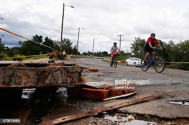 Cyclists ride next to debris from homes destroyed after cyclonic winds on April 22 2015 in Dungog Australia Three people have died and more than...