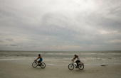 Cyclists ride on the beach in advance of the arrival of Hurricane Wilma which is churning in the Gulf of Mexico as a Category 2 storm October 23 2005...