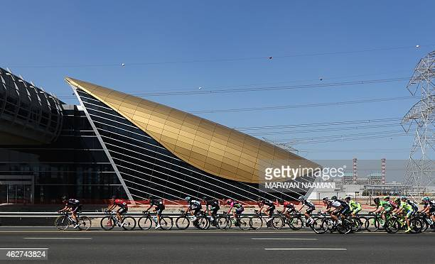 Cyclists ride past a Dubai metro station during the first stage of the Dubai Tour from Dubai International Marina to Union House Flag on February 4...