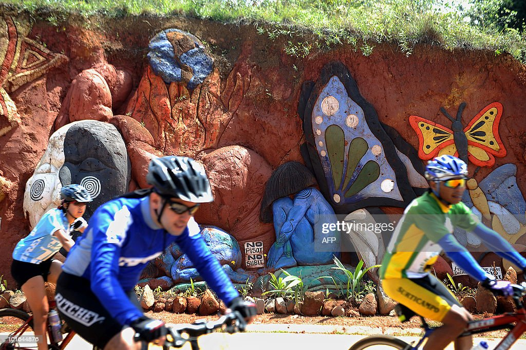 Cyclists ride past a piece by Colombian artist Carlos Andres Gomez during World Environment Day in Cali, Valle del Cauca departament, Colombia on June 5, 2010. Gomez sculpts figures on the mountain to raise awareness of the importance of the environment. AFP PHOTO/Luis ROBAYO