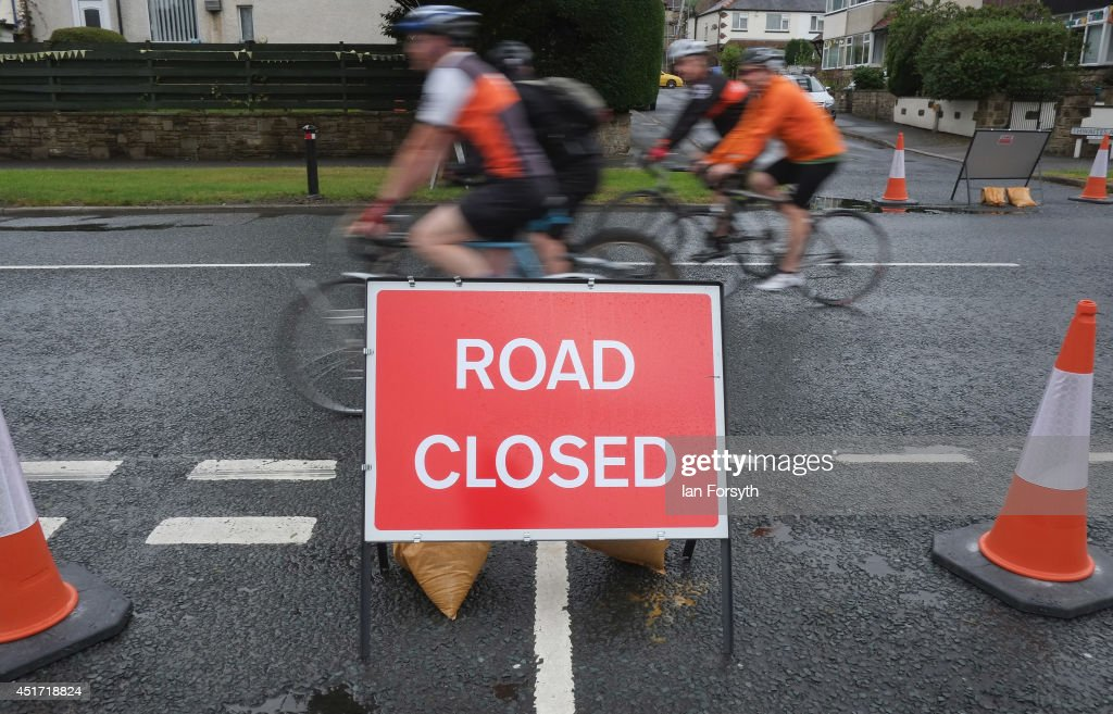 Cyclists ride past a road closure as spectators and residents prepare themselves and gather on the streets as they get ready to watch Stage 1 of the Tour de France on July 5, 2014 in Ilkley, United Kingdom. The world's greatest cycle race, the Tour de France starts for the first time in its history in Yorkshire this weekend . The event is expected to bring thousands of cycling fans to the region.