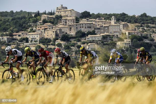 Cyclists ride past a village during the 2225 km nineteenth stage of the 104th edition of the Tour de France cycling race on July 21 2017 between...