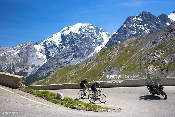 Cyclists ride roadbikes behind motorcycle uphill on The Stelvio Pass Passo dello Stelvio Stilfser Joch in the Alps Italy