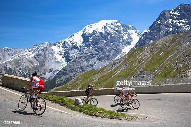 Cyclists ride roadbikes uphill on The Stelvio Pass Passo dello Stelvio Stilfser Joch in the Alps Italy