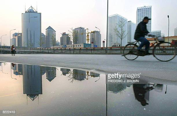 Cyclists ride the quiet streets of Beijing at daybreak past a pool of water reflecting the city's emerging architecturual style 06 April 2004 China's...