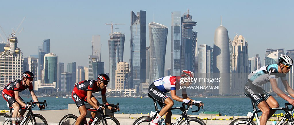 Cyclists ride their bikes in front of skyscrapers during the last stage of the 2013 Tour of Qatar, from Cyline beach to the Doha Cornich, on February 8, 2013. Isle of Man racer Mark Cavendish, of the Omega Pharma team, sealed overall victory on the Tour of Qatar after winning the sixth and final stage. AFP PHOTO MARWAN NAAMANI