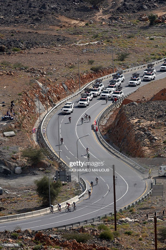 Cyclists ride their bikes in front of the teams' cars during the fourth stage of the Tour of Oman, on February 14, 2013, in Oman. The fourth stage is a 152.5km ride through the mountains from Al Satiyah to the finish line at the peak of a stiff climb at Jabal Al Akhdar.