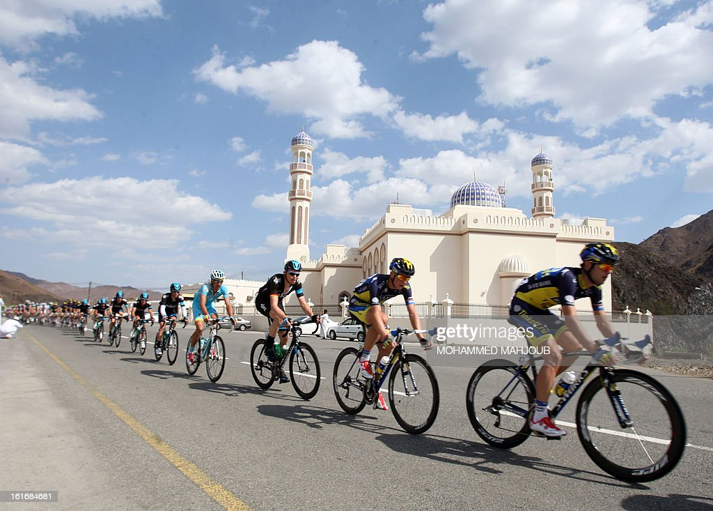 Cyclists ride their bikes past a mosque during the fourth stage of the Tour of Oman, on February 14, 2013, in Oman. The fourth stage is a 152.5km ride through the mountains from Al Satiyah to the finish line at the peak of a stiff climb at Jabal Al Akhdar.