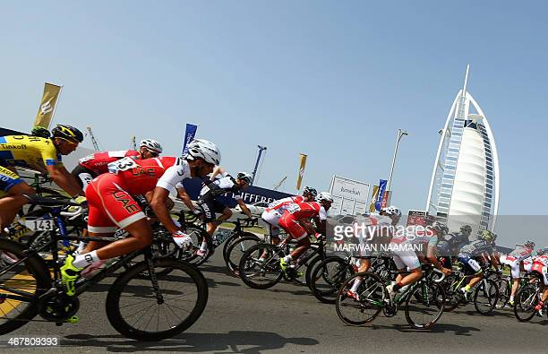 Cyclists ride their bikes past Burj alArab Hotel one of the icons of Dubai during the fourth and last stage of the Dubai Cycling Tour 2014 on...