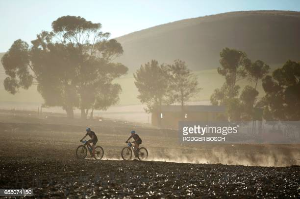 TOPSHOT Cyclists ride through wheat fields during the prologue stage of the 2017 Cape Epic mountain bike stage race near Durbanville on March 19 in...