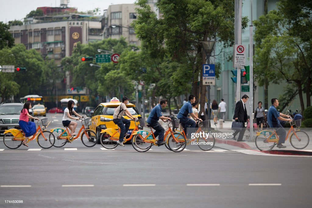 Cyclists ride YouBike rental bicycles on Hsin Yi Road in Taipei, Taiwan, on Wednesday, July 24, 2013. Taiwan President Ma Ying-jeou ruled out driving down the Taiwan dollar to boost exports following the currencys rally against the yen and said the government still aims for growth of at least 2 percent this year. Photographer: Jerome Favre/Bloomberg via Getty Images