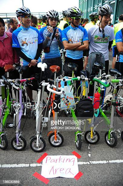 Cyclists stand behind their foldable bicycles as they prepare to cycle along Victoria Harbour in support of a new cycle path in Hong Kong on December...