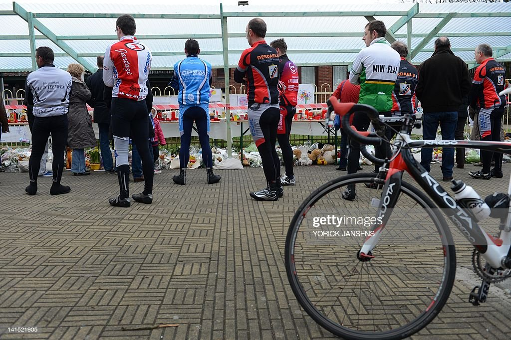 Cyclists stand in front of a shelter, made by the Lommel fire force to protect the tributes, drawings, flowers and candles, for the victims of the Swiss bus crash in front of the 't Stekske primary school in Lommel on March 18, 2012. Twenty-eight people were killed when a coach packed with schoolchildren crashed in southern Switzerland as they returned to Belgium from a skiing holiday, Swiss police said. Twenty-two children were killed in the accident, which happened when the bus inexplicably swerved and hit a concrete wall while travelling through a tunnel late on March 13. Another 24 children were reported injured in the crash, many seriously.