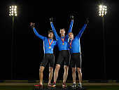 Cyclists standing on podium, celebrating first place