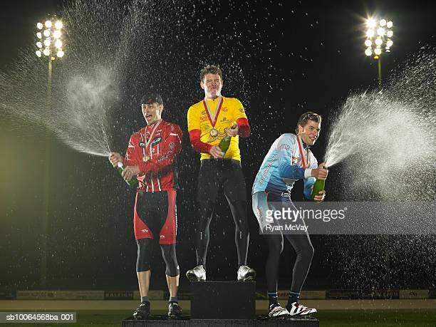 Cyclists standing on podium, spraying champagne