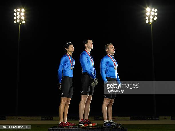 Cyclists standing on podium with medals