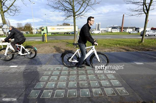 Cyclists use the SolaRoad the first road in the world made of solar panels during the official opening in Krommenie on November 12 2014 The...