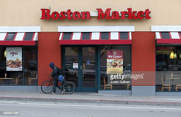 A cyclists walks his bicycle by a Boston Market restaurant on August 21 2012 in San Francisco California Restaurant chain Boston Market announced...