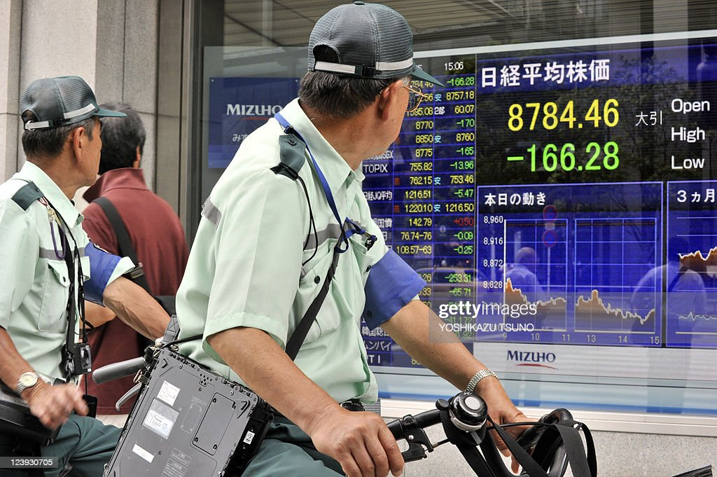 Cyclists watch a share prices board in Tokyo on September 5 2011 Japan's share prices fell 16628 points to close at 878446 points at the Tokyo Stock...