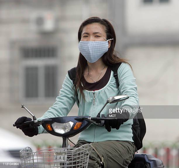 Cyclists wear masks during a day of heavy air pollution in Beijing China May 30 2005 Choking on vile air sickened by toxic water citizens in some...