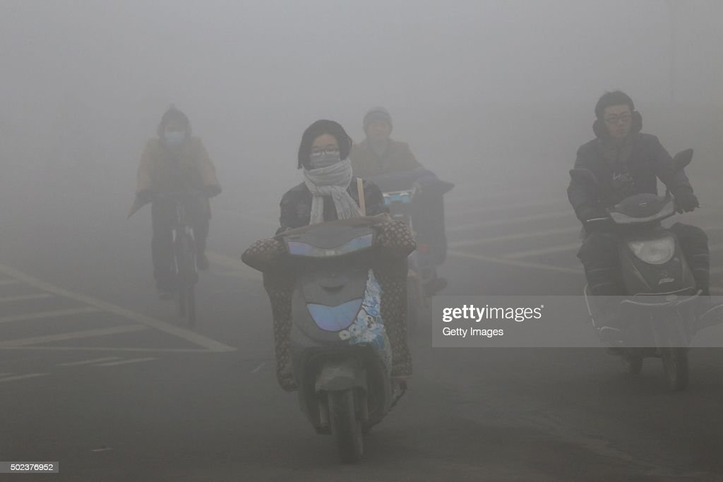 Cyclists wearing masks ride along a road in heavy smog on December 23 2015 in Zhengzhou China According to the Ministry of Environmental Protection...