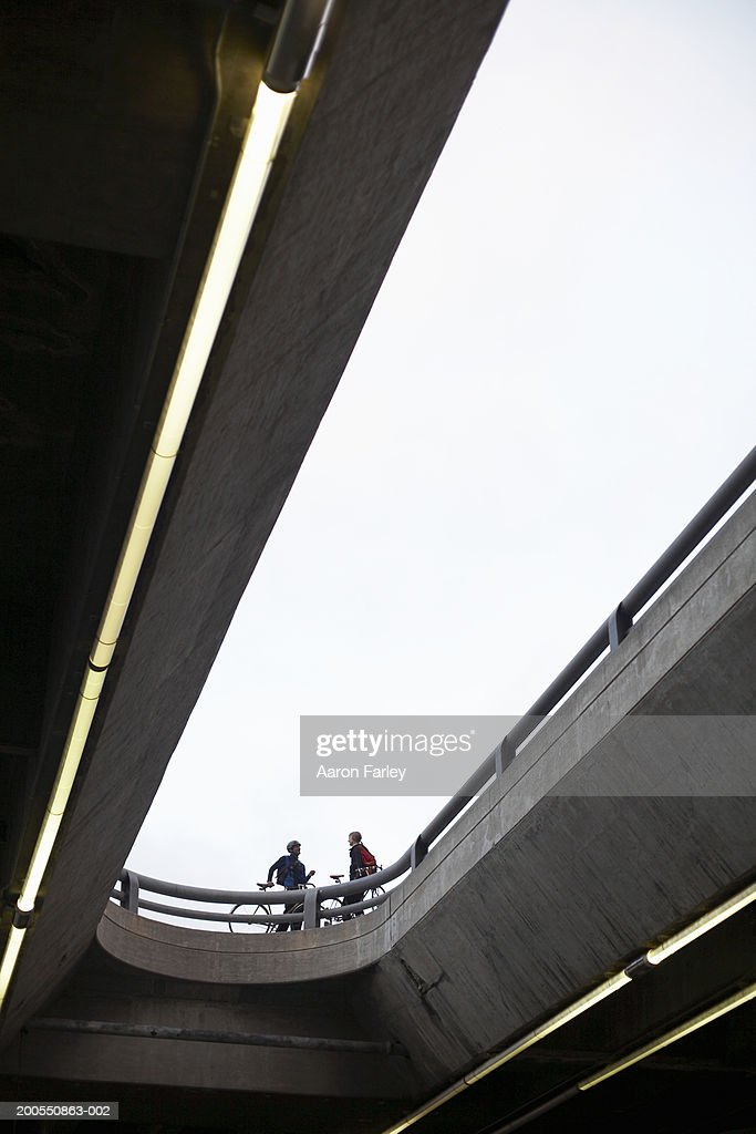Cyclists with bikes standing by bridge railing, low angle view : Stock Photo