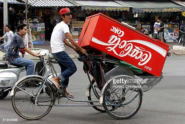 A cyclo driver carries a promotional CocaCola refrigerator on his cyclo in Ho Chi Minh City 27 April 2000 25 years after the fall of Saigon and the...