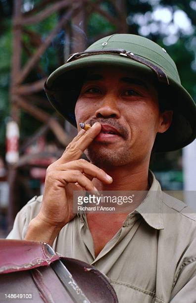 Cyclo driver wearing Viet Cong helmet and  smoking cigarette.