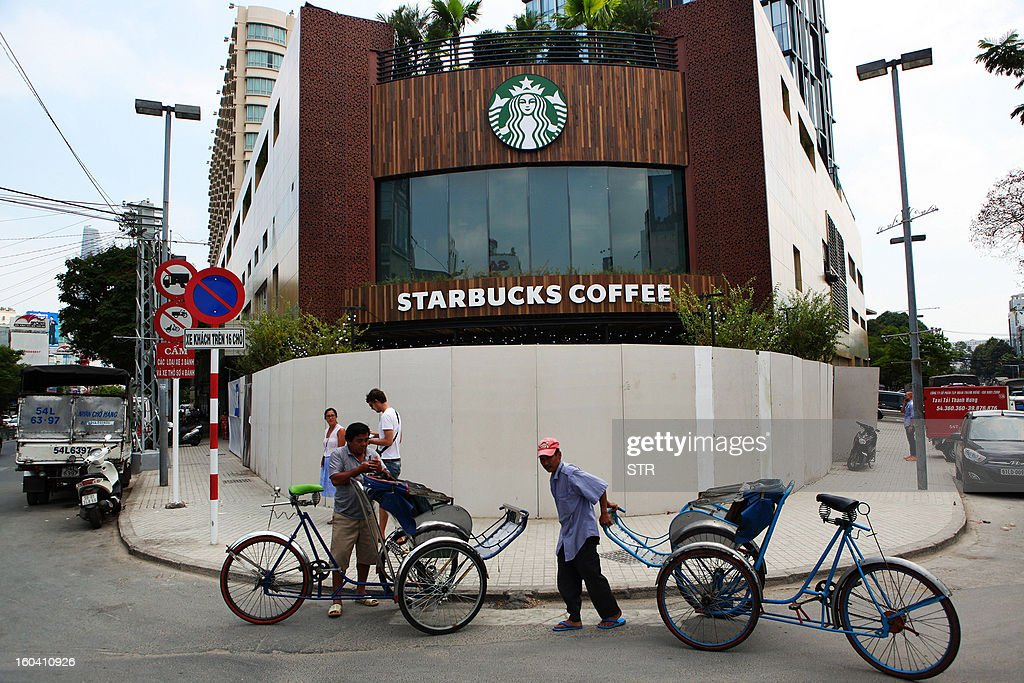 Cyclo drivers wait for customers on a street outside the first Starbucks cafe in Ho Chi Minh city on January 31, 2013 ahead of its official opening on February 1. Starbucks said earlier this month, on January 3, it would open its first store in Vietnam next month, seeking a foothold in the coffee-loving country as part of efforts to expand in Asia. AFP PHOTO