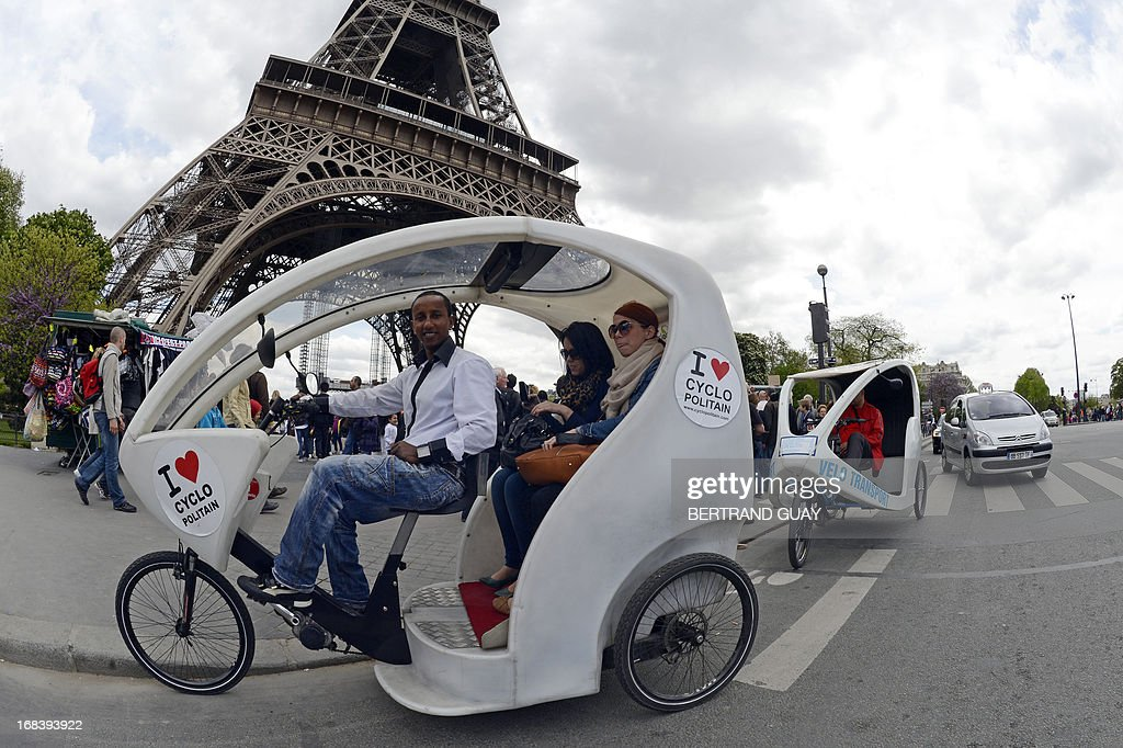 A cyclo taxi poses with customers in front of the Eiffel Tower on May 9, 2013 in Paris.