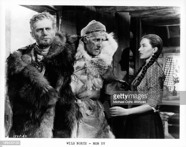 Cyd Charisse opening the door for the freezing Wendell Corey and Stewart Granger in a scene from the film 'The Wild North' 1952