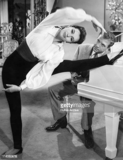 Cyd Charisse US actress and dancer holding a ballet pose standing on one leg with the other leg outstretched and resting on a piano at which sits US...