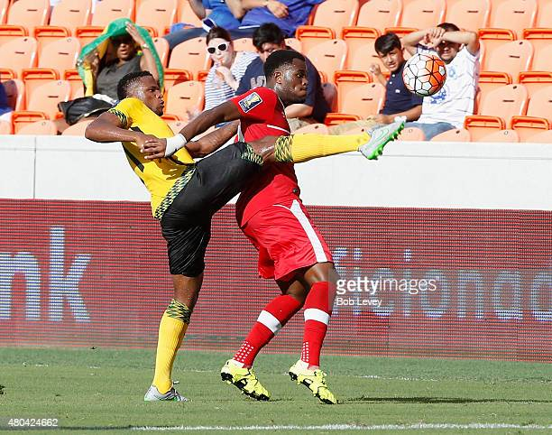 Cyle Larin of Canada and Jermaine Taylor of Jamaica attempt to gain possession of the ball in the first half at BBVA Compass Stadium on July 11 2015...